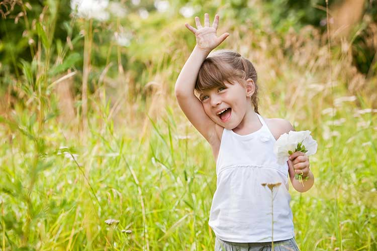 A young girl in a field waving.